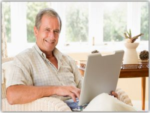 Man sitting in an armchair accessing his laptop computer