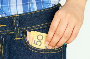 man with his left hand on $50 notes poking out of his jeans pocket