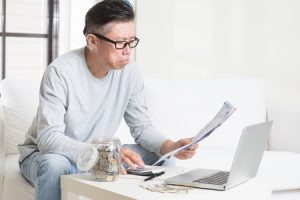 worried 50s mature asian man looking at the bills